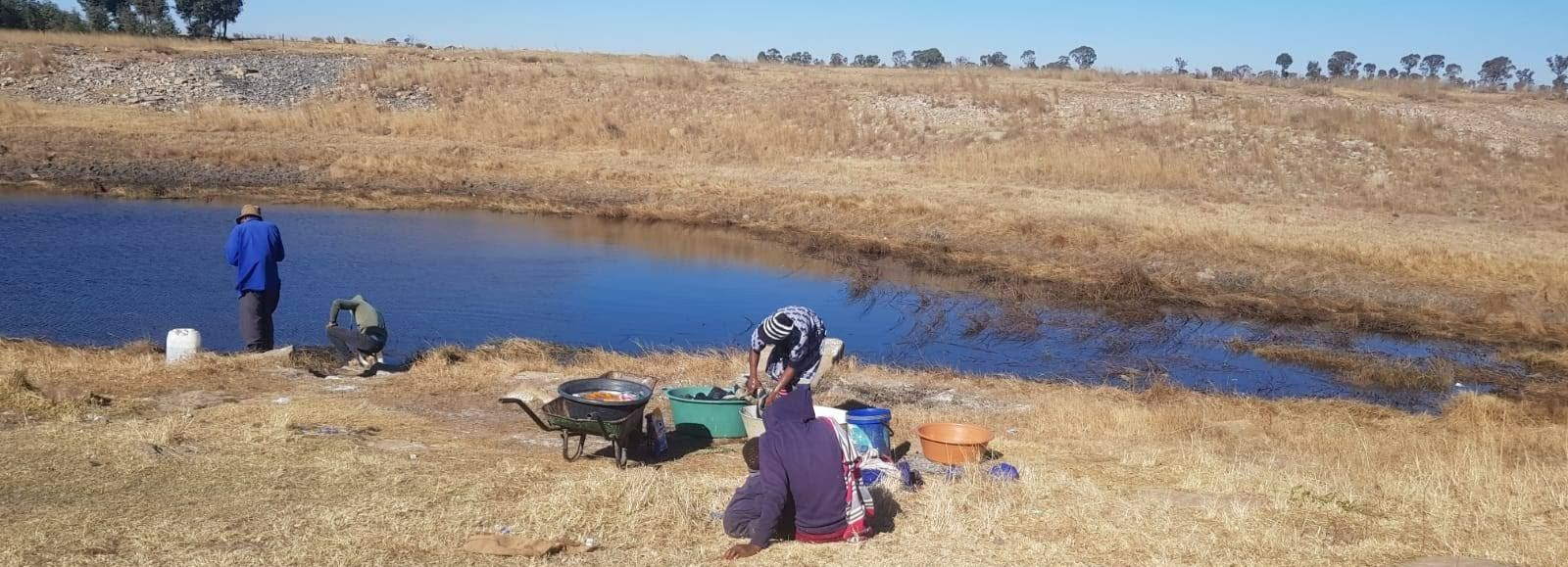 Men collect water at a pond while a lady washes her clothes